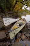 Two canoes rented from Algonquin Outfitters rest along the banks of the Oxtongue River in Ontario, Canada filled with the necessary equipment.