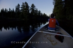 A woman enjoys the quietness and scenery while traveling in a canoe along a river between Whitefish Lake and Rock Lake in Algonquin Provincial Park in Ontario, Canada.