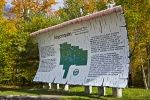 A unique shaped sign on display at the West Gate of Algonquin Provincial Park in Ontario, Canada surrounded by the fall coloured trees.