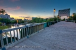 The sunset view of The Forks from the Historic Rail Bridge located in the City of Winnipeg in Manitoba, Canada. The bridge is traffic free and is used as a pedestrian crossing which spans the Assiniboine River.