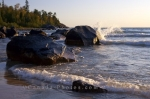 Large boulders create a wall for the water before reaching the beach at Katherine Cove in Lake Superior Provincial Park in Ontario, Canada.