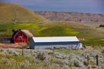 A bright red barn and a long farm building sit amongst the acreage on this ranch in the Big Muddy Badlands near Castle Butte in Southern Saskatchewan, Canada.