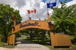A large sign adorned with flags leads to the boardwalk path which takes visitors to Lake Winnipeg in the town of Winnipeg Beach in Manitoba, Canada.