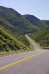 Near Grande Falaise, the Cabot Trail winds through green hillsides around the northern end of Cape Breton Island in Nova Scotia.