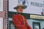 A handsome Canadian Mountie in his full uniform poses for the camera at the Klondike Gold Rush National Historic Site in Dawson City in the Yukon Territory.