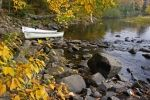 Two canoes sit on the bank of the Oxtongue River in Oxtongue River-Ragged Falls Provincial Park in Ontario, Canada surrounded by the Autumn colors.