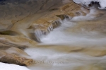 Water rushes over the rock formations in the creek in Johnston Canyon in Banff National Park in Alberta, Canada from Spring time thawing.