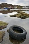 A car tire litters the harbour, adding to the ocean pollution along the shoreline in Great Brehat on the Great Northern Peninsula of Newfoundland, Canada.