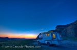 People traveling in a camper can sit inside while enjoying the scenery of the beautiful colors highlighting the sky at dusk near Castle Butte in the Big Muddy Badlands in Saskatchewan, Canada.