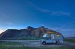 Tourists visiting the Big Muddy Badlands in Southern Saskatchewan pull up in a camper to enjoy the beauty of Castle Butte in the lighting at dusk.