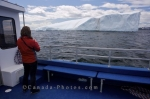 A woman aboard the Gaffer III on a tour that takes passengers to Iceberg Alley to see the miracle world in the waters of the Great Northern Peninsula in Newfoundland, Canada.