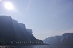 A haze blocks the sun over Western Brook Pond in Newfoundland Labrador masking the cliffs with a unique lighting.