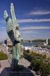 From atop the Notre-Dame-de-Bon Secours Chapel in Old Montreal, Quebec, an angel statue watches over the harbour where the clock tower and yacht club are located.