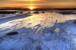 A beautiful winter scene is the sunset that takes place over a frozen lake in the Churchill Wildlife Management Area in Churchill, Manitoba.