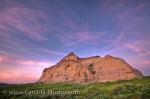 The colorful sky at sunset adds to the unique geological feature of Castle Butte in the Big Muddy Badlands in Saskatchewan, Canada.
