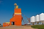 A brightly colored grain elevator and three large cylinders located in the small town of Coronach in Southern Saskatchewan, Canada.