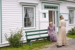 Costumed interpreters chat outside one of the historic houses in the Sherbrooke Village Museum in Nova Scotia, Canada.