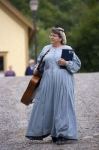 A costumed woman is a musician in the historic Sherbrooke Village Museum in Nova Scotia, Canada who entertains the visitors.