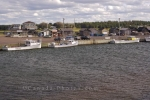 The quaint waterfront at Covehead Bay in Prince Edward Island in Canada where you will find boats moored at the wharf and a boardwalk ideal for an afternoon walk.