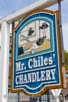 A bright, blue sign made of wood hangs outside the shop known as Mr. Chile's Chandlery located in Discovery Harbour in Midland, Ontario in Canada.