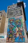 On the side of the building housing the Hotel McLaren in the downtown core of the City of Winnipeg, Manitoba, a colorful wall mural is highlighted below the black and white sign.