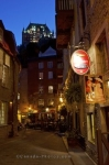 The evening street lights glow along the Rue Notre-Dame in Old Quebec in Quebec City, Canada as the rooftop of the Fairmont Le Chateau Frontenac adorns the backdrop.