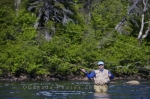 A fisherman enjoying the sunshine and the wilderness as he stands in the White Bear River Falls in Southern Labrador fly fishing.