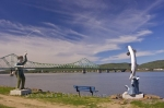 A fisherman and an Atlantic Salmon statue displayed along the river bank in Restigouche, New Brunswick with the J.C. Van Horne Bridge as a backdrop.