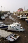 At low tide in the town of Halls Harbour in the Bay of Fundy in Nova Scotia, Canada, fishing boats tied to the wharf remain stranded until the tide changes.