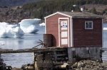 A fishing stage sits along the waters edge in Conche Harbour on the Great Northern Peninsula in Newfoundland, Canada with pack ice floating aimlessly in the background.