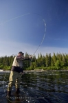 A man enjoys the day fly fishing under the bright sun that surrounds the region of the White Bear River Falls near the Rifflin'Hitch Lodge in Southern Labrador, Canada.