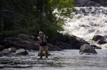 A man enjoys the outdoor sport of fly fishing as he casts his line near the White Bear River Falls in Southern Labrador in Newfoundland Labrador, Canada.