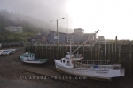 A fog bank sits above Halls Harbour in the Bay of Fundy in Nova Scotia, Canada as boats remain tied to the wharf.
