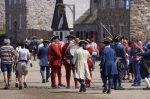 Many tourists and costumed animators fill the quay at the Fortress of Louisbourg along the Fleur de lis Trail in Cape Breton, Nova Scotia.