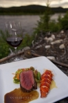 A dinner entree is served to the guests by the gourmet chef at the Rifflin'Hitch Lodge in Southern Labrador, Canada on the outside terrace overlooking the Eagle River.