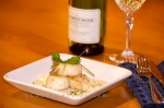 The ideal gourmet entree is a beautifully laid out plate of seared scallops topped with hollandaise sauce which is best accompanied by a glass of white wine.