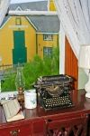 The guest bedroom window at the Alpaheus Barbour House at the Barbour Living Heritage Village in Newfoundland, Canada is adorned with an antique typewriter, lantern and a view of another historic building.