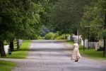 A woman dressed in historic clothing wanders the street in the Sherbrooke Village Museum in the town of Sherbrooke in Nova Scotia, Canada.