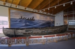 Artifacts dating back to the whaling years around Labrador are on exhibit at the Interpretation Centre at the Red Bay National Historic Site. At this display, a historic whaling boat used by the Native Indians is towered over by a wall mural.