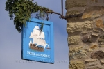 A sign hangs from the stone building advertising the Hotel de la Marine Restaurant at the Fortress of Louisbourg in Nova Scotia, Canada.