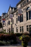 Flags, flowers and gardens adorn the exterior of the historic building which is home to the Hotel de Ville or City Hall in Old Quebec, Canada.