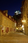 The lights from the hotel known as the Fairmont Le Chateau Frontenac tower over the streets of the Rue Notre-Dame in Quebec City, Canada.