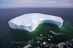 An aerial picture of an iceberg floating in the Strait of Belle Isle in Southern Labrador, Canada with chunks of ice breaking away.