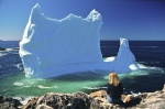 A woman sits atop a rock viewing a large chunk of ice in the Iceberg Capital of the world known as Twillingate, Newfoundland.
