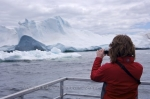 A tourist aboard an Iceberg Watching boat tour takes her own set of pictures of these massive pieces of ice in Iceberg Alley in Newfoundland, Canada.