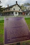 An information sign detailing important facts about Joseph Schneider Haus, a National Historic Site in Kitchener, Ontario, stands outside the white picket fence.