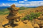 An inukshuk sits upon a steep hill above the Tablelands Trail in Gros Morne National Park on the Great Northern Peninsula of Newfoundland Labrador, Canada.