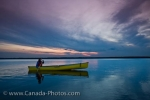 A woman canoeing on the calm waters of Lake Audy in Riding Mountain National Park in Manitoba, Canada during an intriguing sunset.