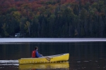 A woman enjoys a canoe adventure in the tranquility of Rock Lake in Algonquin Provincial Park in Ontario where she is surrounded by the autumn colors of the forest.
