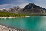 The sharp peaks of the Canadian Rocky Mountains tower above the beautiful scenery of Lake Minnewanka in Banff National Park in Alberta, Canada.